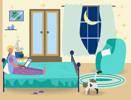 A man in pajamas works on a laptop at home in the bedroom on the bed. Freelance concept, quarantine due to covid-19.