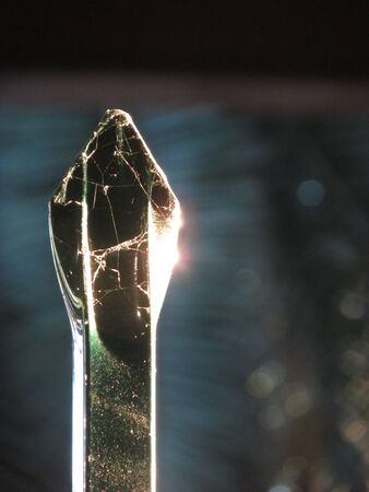 Close-up shot of golden sunlight reflecting off the sharp tip of a gate