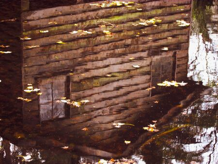 Water reflection of an eerie looking empty boat shack. Located in Sherbrooke, a rural town in Victoria, Australia. The autumn season gives sepia tint to the image. Suitable for Halloween themed artwork background Stock Photo