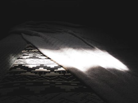 Sunlight coming from the bedroom window illuminates the layer of sheets on a comfy bed. Suitable to illustrate the concept of slumber, nap or snooze
