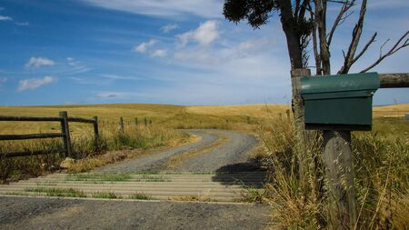 Windy driveway to enter a farmland with picturesque hills in the backgrorund. Summer in Australia is marked by lack of rain and constant heat