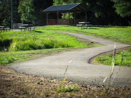 Walkway leading to a shelter in a public park. Suitable to illustrate an article about dream interpretation or psychology. Footpath in a dream symbolizes a new way to solve current or previous issues