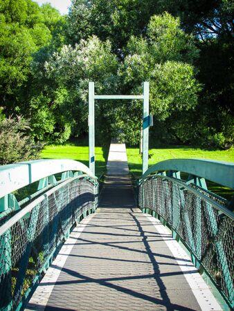 Metal pedestrian bridge over Meander River. The bridge is located near Deloraine Apex Caravan Park. On the other side of the bridge is Deloraine Rotary Park Reserve. Deloraine is a tourist destination