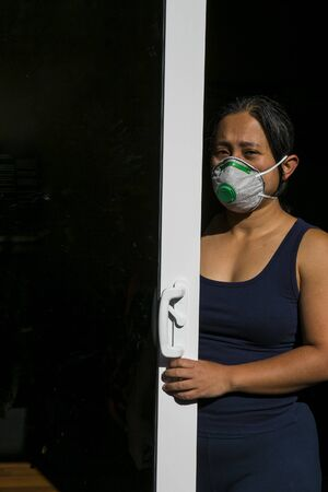 A concerned woman stands behind glass door with face mask. Suitable to depict self-quarantine at home during coronavirus pandemic. A light touch of blur is intentional to illustrate restlessness
