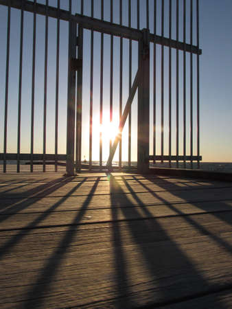 The afternoon sun casts shadows of the barrier bars of the Seaford beach jetty. The barrier is a recent construction to the platform. Visitors used to be able to stand at the edge of the jetty's end.