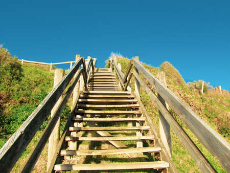 Ground view of wooden beach steps at Sandringham, VIC, Australia. The steps lead to a white sandy beach which is a popular location for beachgoers. This suburb is one of Melbourne's bayside suburbs.