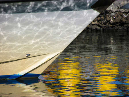 Reflection of calm sea water on a boat's bow as if the boat has multiple tiny cracks. Suitable illustrate optical illusion caused by water on science books or as a background for travel magazines. Stock Photo