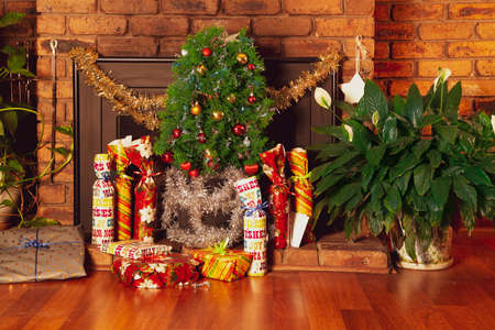 Vintage house decorated with small Christmas tree placed in front of a fireplace. The gifts are arranged on the floor. Suitable to illustrate modest Christmas festivity without depicting people. 版權商用圖片