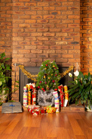 Vintage house decorated with small Christmas tree placed in front of a fireplace. The gifts are arranged on the floor. Suitable to illustrate modest Christmas festivity without depicting people.
