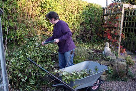 Female gardener clearing the garden for winter Stock Photo