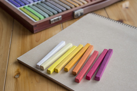 sketchbook: Colorful pastels lined up on a sketchbook and wooden case