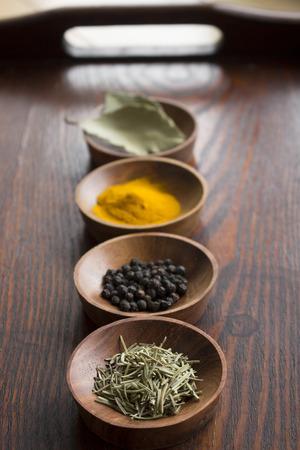 Dry herb served in wooden plate rosemary bay leaf black pepper turmeric