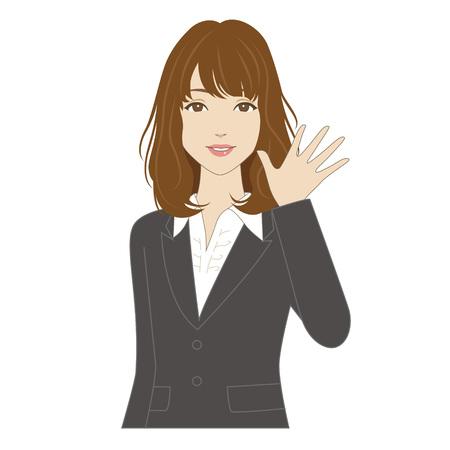 手を振っているビジネス スーツで笑顔の若い女性