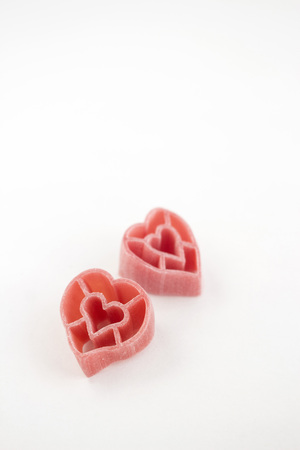 short pasta: Heart shaped pink pasta in white background