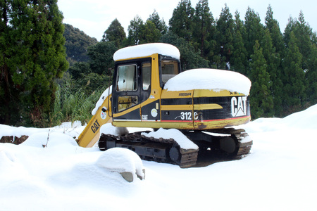power shovel: A yellow power shovel covered by snow