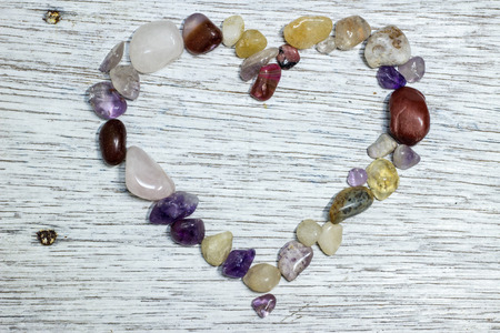 painted wood: Heart shape frame made of gemstones on a antique painted wood board Stock Photo