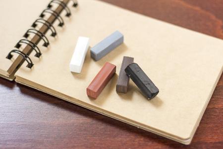 spiral binding: Hard pastels on the sketchbook on a wooden desk