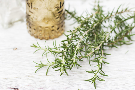 Stylish glass bottles and rosemary on painted wooden table