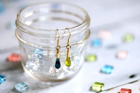 Cute teardrop-shaped earring made of glass and colorful glass tiles Stock fotó