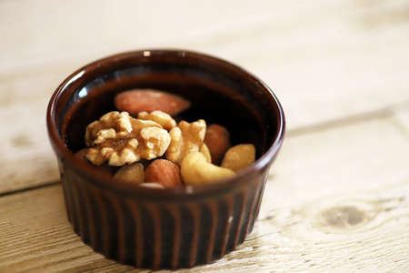 Mixed nuts in the brown cocotte on the antique wooden table