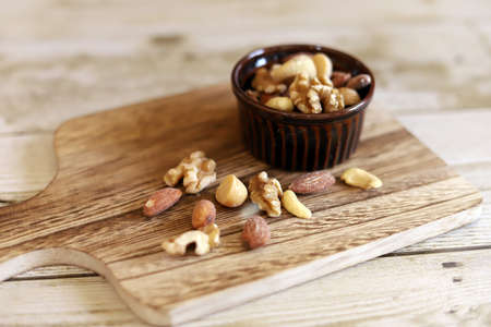 Mixed nuts, brown cocotte and wooden cutting board