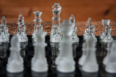 Glass chess set on a black marble board photo