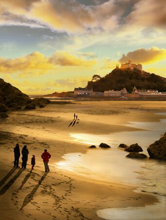 Beautiful evening at St Michaels Mount Cornwall, a family take a walk to watch the sun set and spot two children with their dog,, Zdjęcie Seryjne