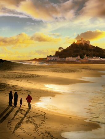 Beautiful evening at St Michaels Mount Cornwall, a family take a walk to watch the sun set,