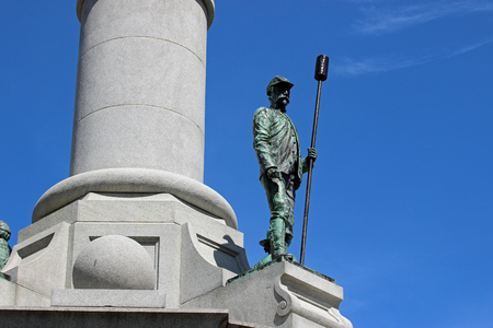 A statue of a union soldier standing tall against a blue sky. Stock Photo