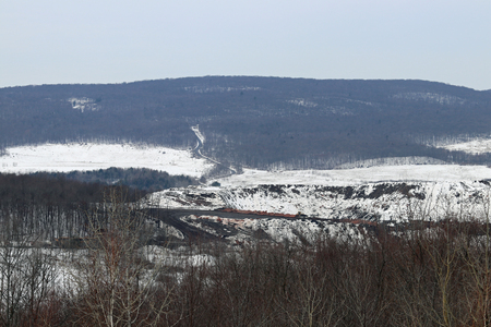 Snowy hills with heavy equipment working on the roads. 写真素材