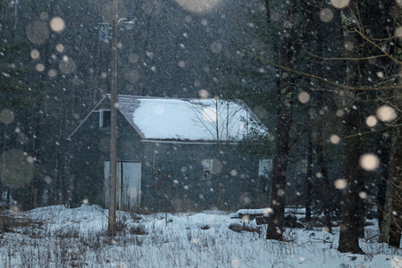 An old building with heavy snow flakes falling around it. 写真素材