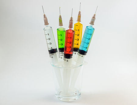 containing: plastic medical syringes containing multicolor solutions in medicine glass with white background