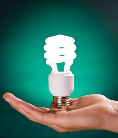 Compact fluorescent lightbulb held by hand on green background
