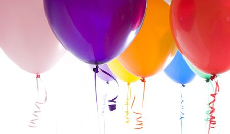 Close up of variety of balloons with ribbons brightly lit Imagens