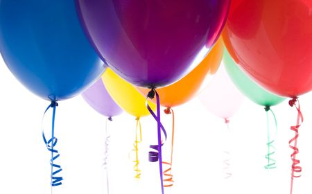 Close up of variety of balloons with ribbons brightly lit photo