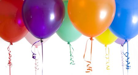 balloon background: Close up of variety of balloons with ribbons brightly lit Stock Photo