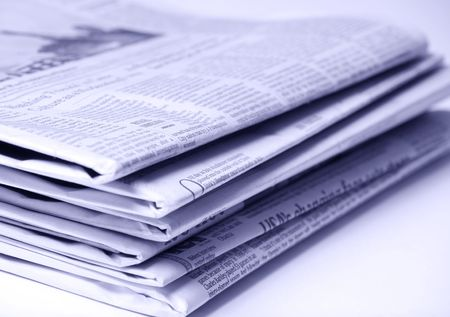 Blue tinted newspapers on light background shot with very shallow depth of focus