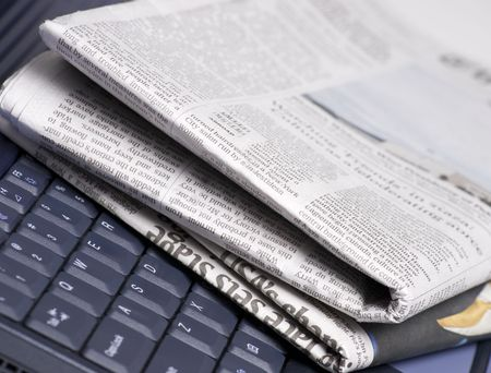 Stack of newspapers with laptop computer