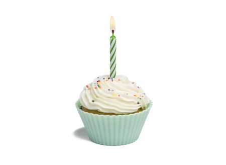 Green cupcake with candle on white background