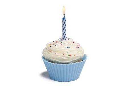 白い背景の上の蝋燭と青のカップケーキ 写真素材