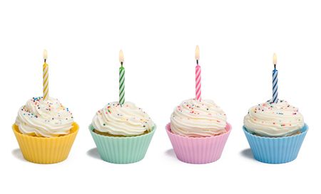 白い背景の上の蝋燭と 4 つのカップケーキ