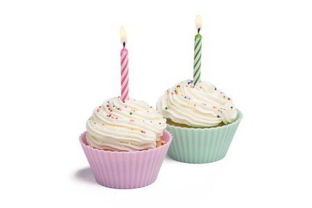 白い背景の上の蝋燭との 2 つのカップケーキ