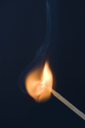 combust: Match starting on fire on a black background