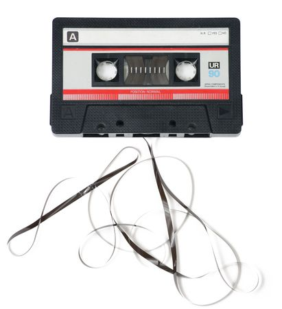 Classic, retro audio cassette with tape coming out on white background