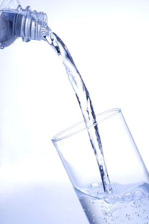 Pouring water into glass with shaded background