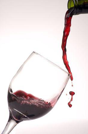 網かけの背景でワインのグラスにワインを注ぐ