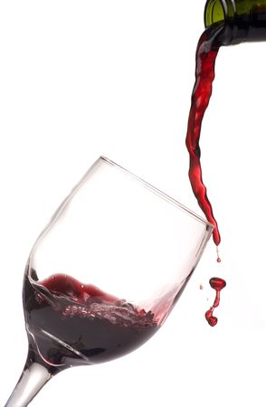 白い背景の上のワインのグラスにワインを注ぐ