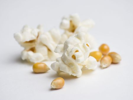 Popped and un-popped popcorn on white