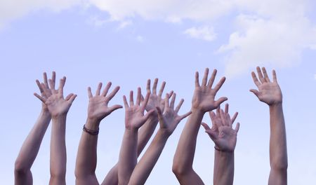 Several hands raised in the air against a beautiful blue sky
