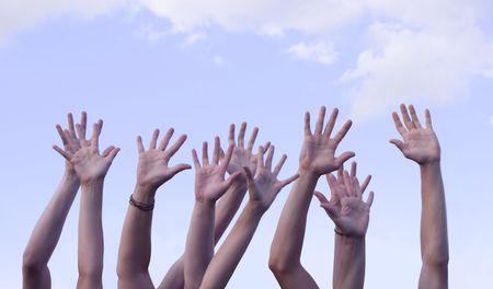 manos levantadas al cielo: Varias manos planteadas en el aire contra un bello cielo azul